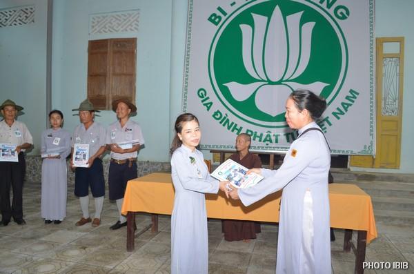 Chị Huynh trưởng Tôn Nữ Thị Hương, Phó Ban Hướng Dẫn, trao Giải thường về thành tích học tập cho các Trại sinh trúng cách, Nữ Htr.Trại sinh này đã ôm con nhỏ đến tham dự Trại Huyền Trang